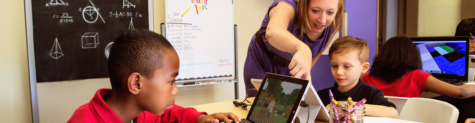 Lifestyle photo of teacher helping student with Minecraft Lesson.