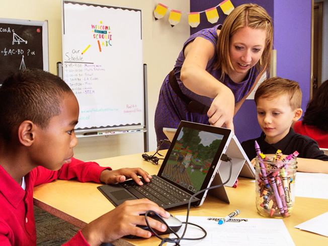 Lifestyle photo of teacher engaging with two smiling students working on computers and using Minecraft: Education Edition worksheets.