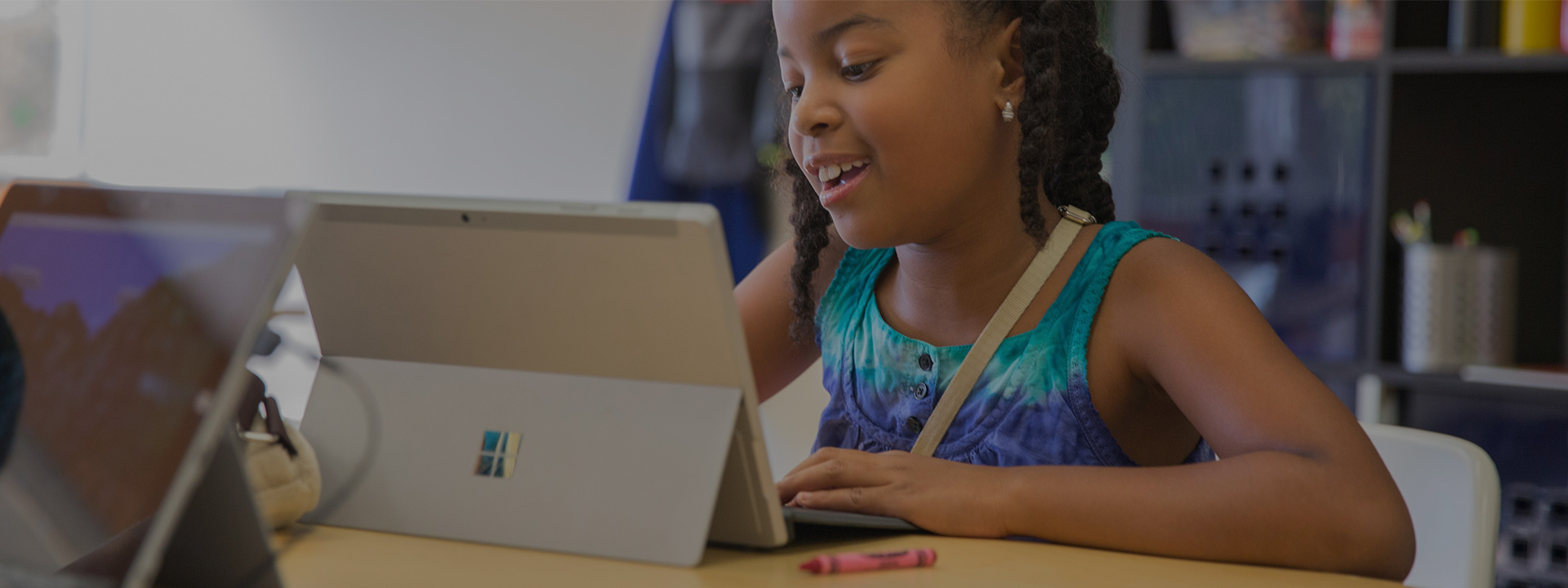 Lifestyle photo of a student at her Microsoft surface tablet playing the game, smiling.