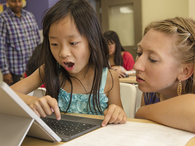 Lifestyle photo of teacher engaging with an excited student playing the game at the student's desk.