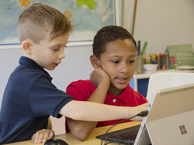 Lifestyle photo of two students sharing a computer and playing the game.