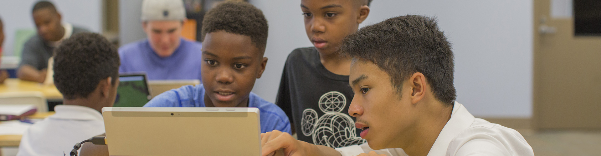 Lifestyle photo of students interacting and playing Minecraft: Education Edition on shared a computer.
