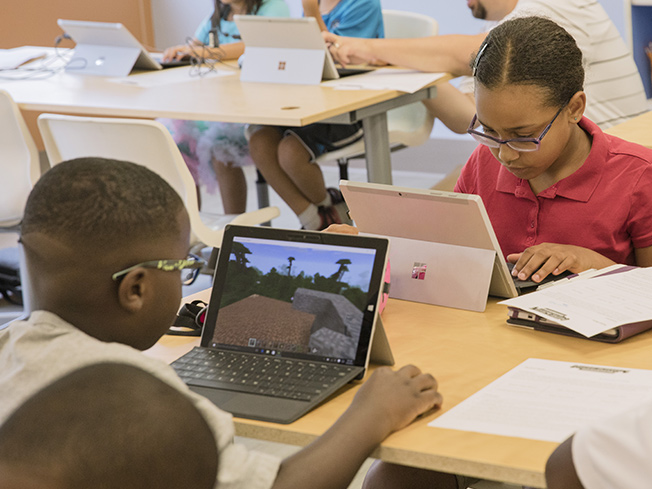 Lifestyle photo of students engaged in playing the game on their computers.